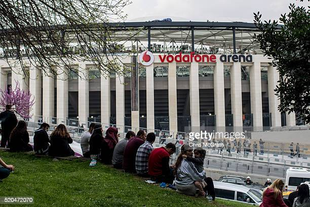 Besiktas fans sit on a hill overlooking the new Vodafone Arena ahead of the opening match between Besiktas and Bursaspor on April 11 2016 in Istanbul...