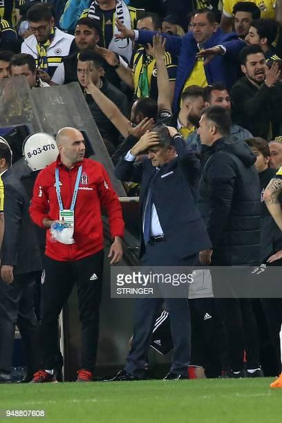 Besiktas head coach Senol Gunes holds his head after being hit by an object during the Ziraat Turkish Cup semi final second leg football match...
