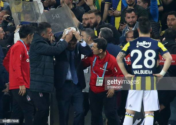 Besiktas head coach Senol Gunes holds his head after being hit by an object during the Ziraat Turkish Cup semi final second leg football match...