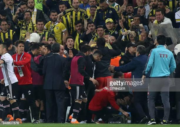 Besiktas head coach Senol Gunes receives first aid after being hit on the head by an object during the Ziraat Turkish Cup semi final second leg...