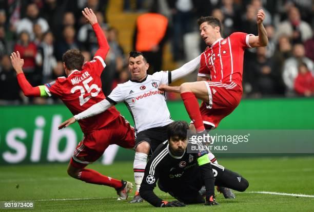 Besiktas midfielder Gary Medel and Besiktas goalkeeper Tolga Zengin fight for the ball with Bayern Munich's German forward Thomas Mueller and Bayern...