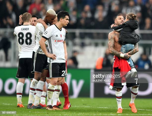 Besiktas midfielder Ricardo Quaresma holds a child as he stands with teammates after the second leg of the last 16 UEFA Champions League football...