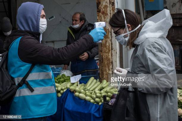 Besiktas municipality police and employees distribute masks check ID's and take the temperature of people arriving at the entrance of the Besiktas...