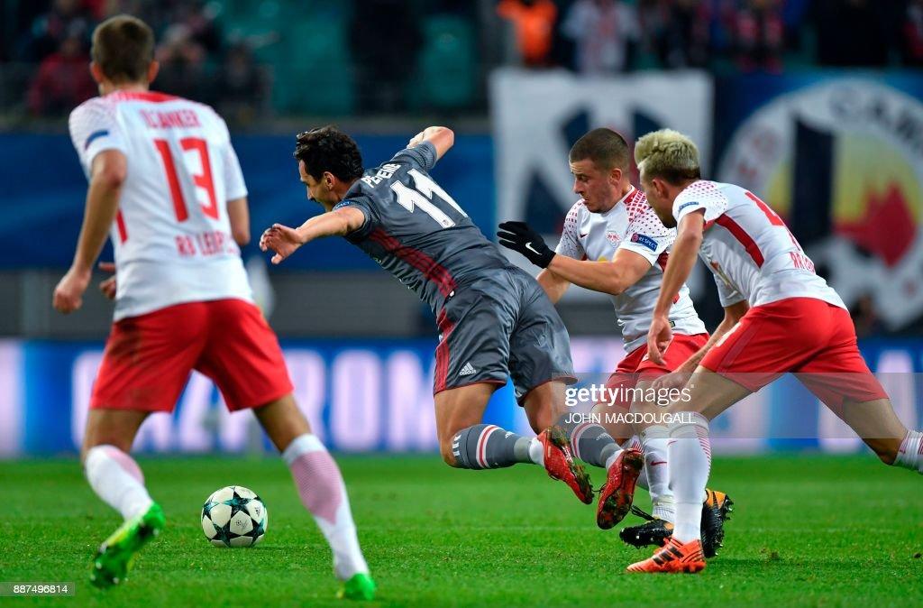 Besiktas' Mustafa Pektemek (C) falls during the UEFA Champions League group G football match RB Leipzig vs Besiktas in Leipzig, eastern Germany, on December 6, 2017. / AFP PHOTO / John MACDOUGALL