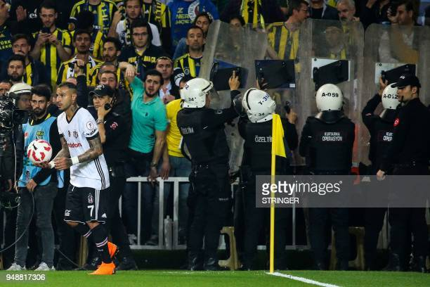 Besiktas Portuguese midfielder Ricardo Quaresma holds the ball near the corner area as Turkish antiriot police officers hold their shields to protect...