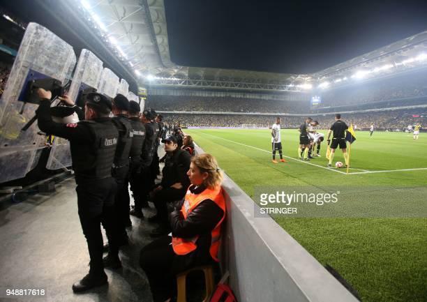 TOPSHOT Besiktas Portuguese midfielder Ricardo Quaresma prepares to kick a corner shot as Turkish anti riot police officers hold their shields to...