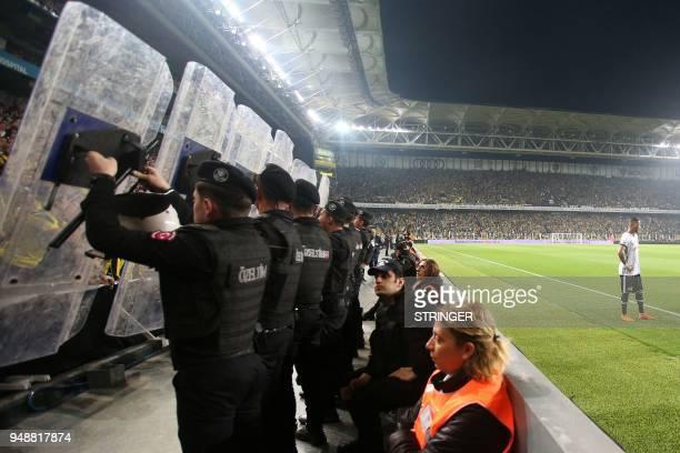 Besiktas Portuguese midfielder Ricardo Quaresma prepares to kick a corner shot as Turkish anti riot police officers hold their shields to protect...