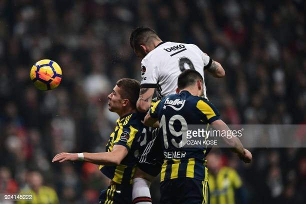 Besiktas' Spanish forward Alvaro Negredo heads the ball next to Fenerbahce's Turkish defender Sener Ozbayrakli and Russian defender Roman Neustaedter...