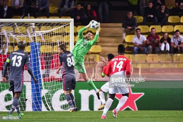 Besiktas' Spanish goalkeeper Fabricio Agosto Ramirez grabs the ball under pressure from Monaco's Colombian forward Radamel Falcao and Monaco's...