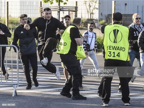 A Besiktas supporter kicks a stadium steward during clashes outside the Parc Olympique Lyonnais stadium prior to the UEFA Europa League football...