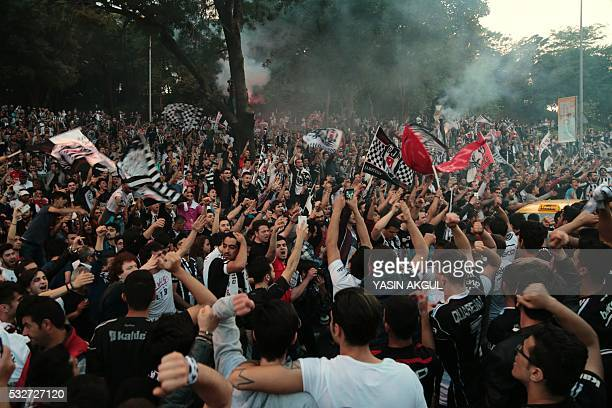 Besiktas' supporters celebrate after their team won the Turkish Super Toto league football match between Besiktas and Osmanlispor at the Vodafone...