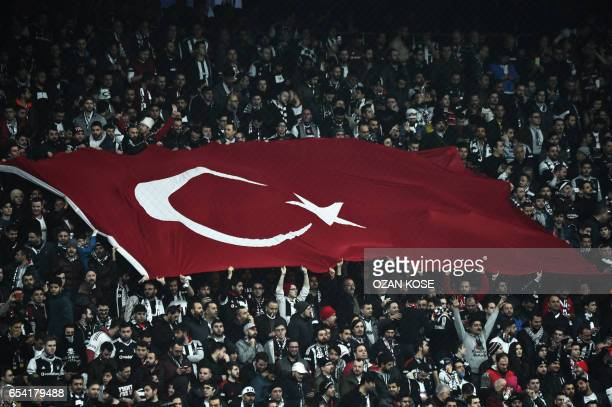 Besiktas' supporters wave a giant Turkish flag during the UEFA Europa League round of 16 second leg football match between Besiktas JK and Olympiacos...