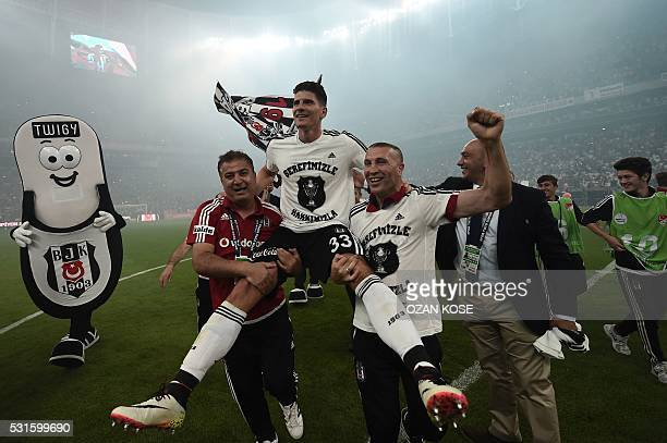 Besiktas's German forward Mario Gomez celebrates with his team the 20152016 champion title after winning the Turkish Super Toto league football match...