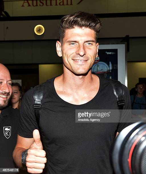 Besiktas's new transfer German striker Mario Gomez greets the fans at the airport as he arrives in Vienna to attend Besiktas' Austria camp on July 31...