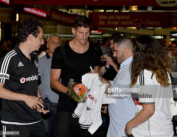 Besiktas's new transfer German striker Mario Gomez signs a fan's Tshirt at the airport as he arrives in Vienna to attend Besiktas' Austria camp on...