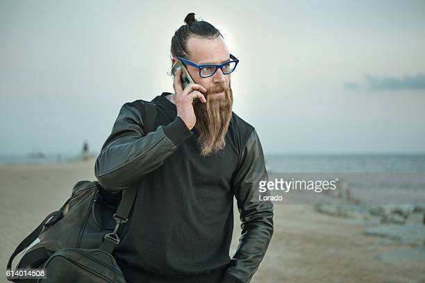 Bespectacled bearded handsome male on smartphone by the sea