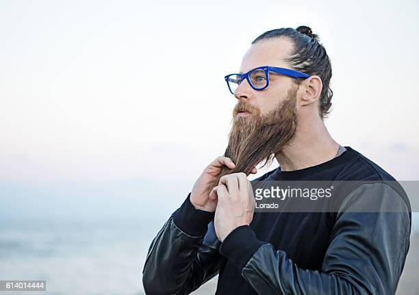 Bespectacled bearded handsome male posing by the sea
