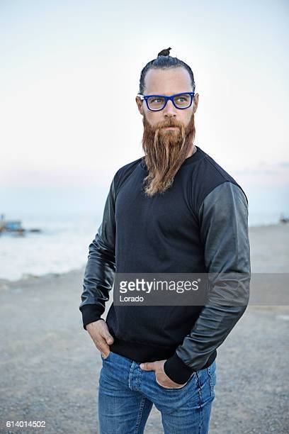 bespectacled bearded handsome male posing by the sea - topknot stock pictures, royalty-free photos & images