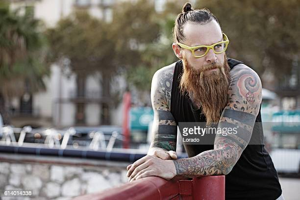 bespectacled bearded handsome male posing in an urban setting - topknot stock pictures, royalty-free photos & images