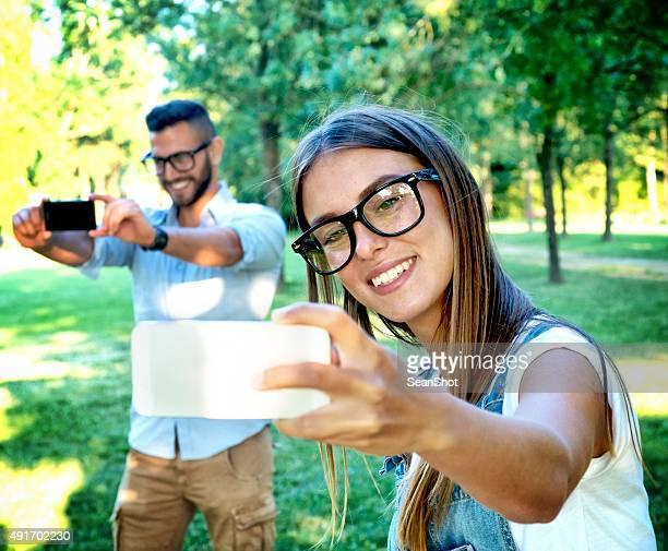 Bespectacled Couple faisant un Double Selfie dans le parc