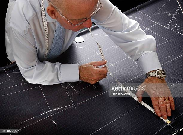 Bespoke Head Cutter Peter O'Neill marks out and cuts a suit pattern at Gieves and Hawkes on Saville Row on August 13 2008 in London England A bespoke...