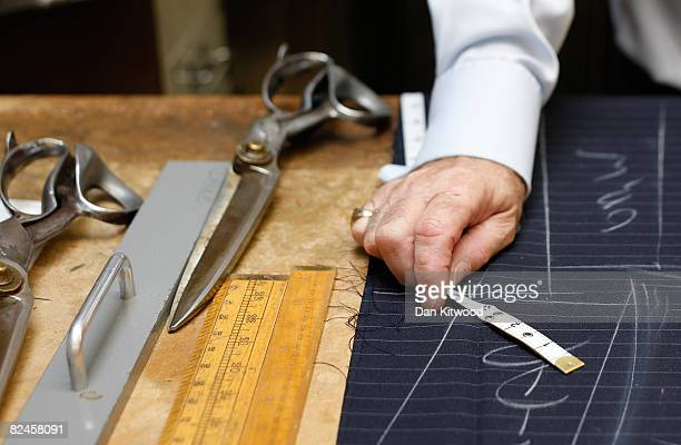 Bespoke Head Cutter Peter O'Neill marks out and cuts a suit pattern at Gieves and Hawkes on Savile Row on August 13 2008 in London England A bespoke...