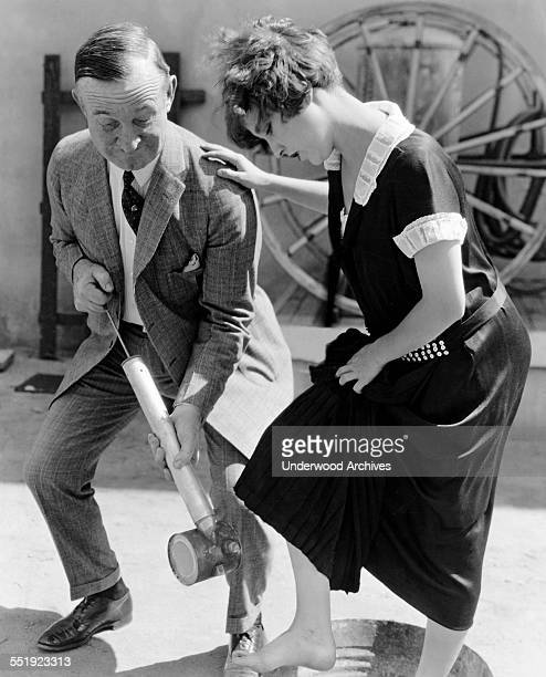 Bessie Love gets sprayed for hoof and mouth disease by Charlie Murray after they were filming in Texas along with 50000 head of cattle as extras in...