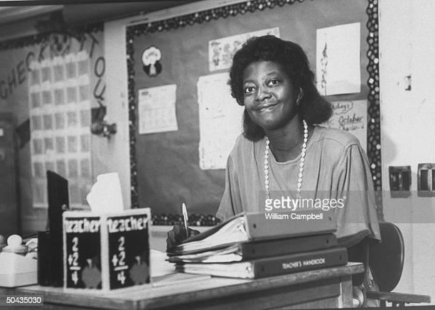 Bessie Pender a former school janitor who put herself through college to become a teacher w pen in hand as she works on lesson plans at desk at...