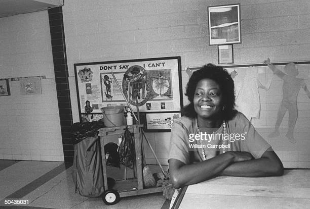 Bessie Pender a former school janitor who put herself through college to become a teacher sitting at desk w janitor's cart in the bkgrd in the hall...