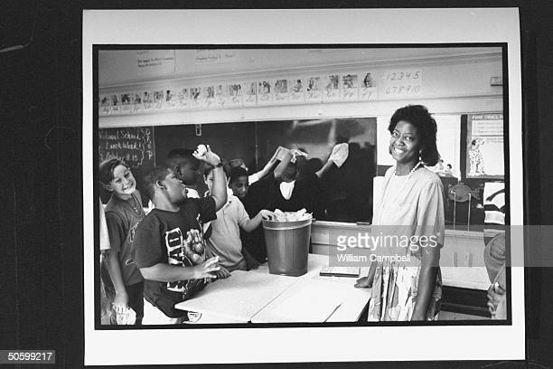 Bessie Pender a former school janitor who put herself through college to become a teacher looking on as students put trash into dustbin resting on...