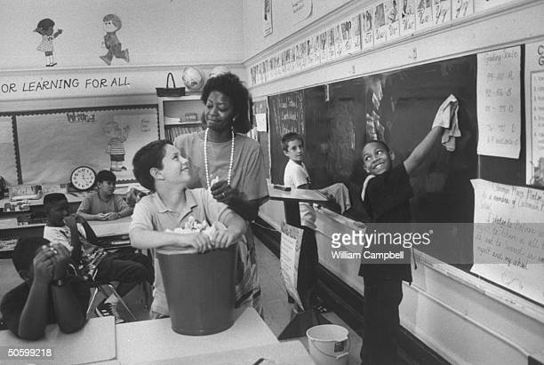 Bessie Pender a former school janitor who put herself through college to become a teacher cuddling unident student who is holding dustbin filled w...