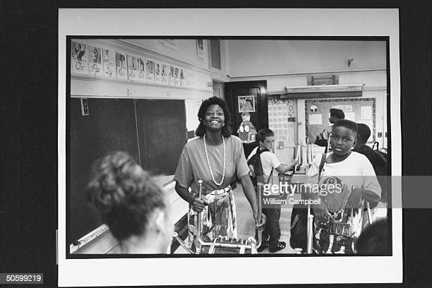 Bessie Pender a former school janitor who put herself through college to become a teacher placing overturned chairs on top of desk as students do the...