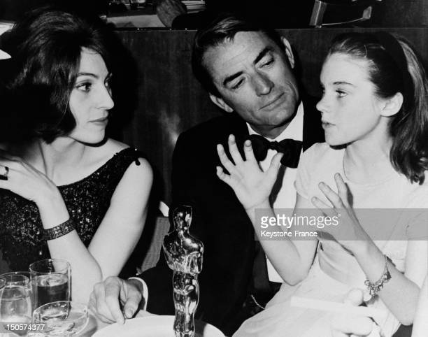 APRIL 12 Best actor Gregory Peck with his Oscar statuette seated between his wife Veronique Passani and actress Mary Badham in movie 'To Kill A...