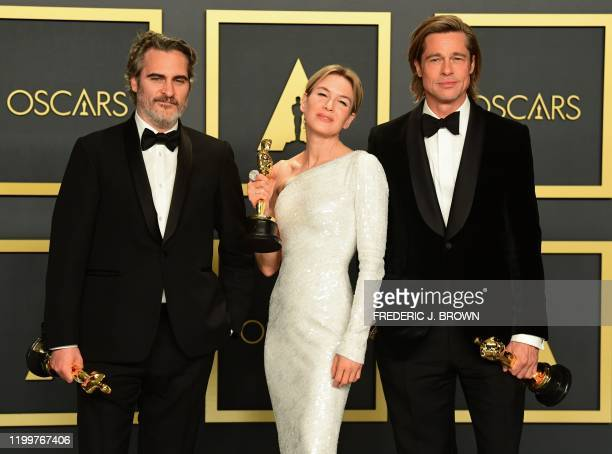 TOPSHOT Best Actor Joaquin Phoenix Best Actress Renee Zellweger and Best Supporting Actor Brad Pitt pose in the press room with their Oscars during...