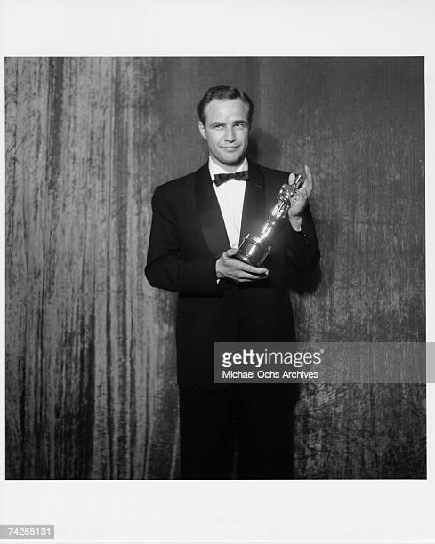 Best actor winner Marlon Brando poses backstage at the 27th Academy Awards holding an Oscar for his performance in the movie On The Waterfront on...