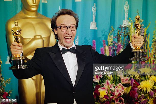Best Actor winner Roberto Benigni for Life is Beautiful holds onto Oscar statuettes at the 71st Annual Academy Awards Ceremony