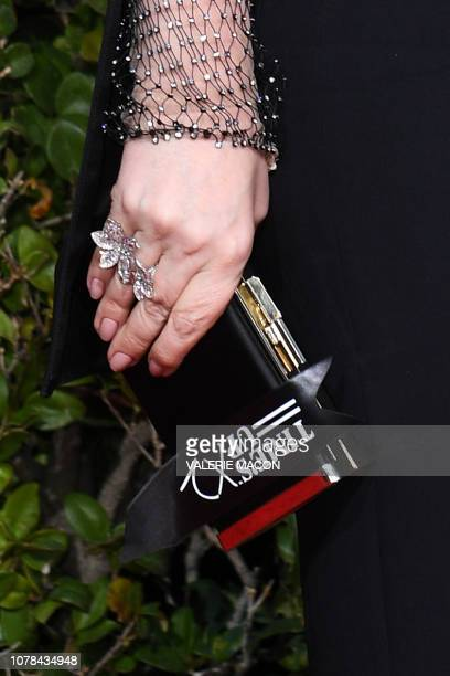 Best Actress in a Motion Picture Musical or Comedy for The Favourite nominee Olivia Colman holds a Time's Up ribbon as she arrives for the 76th...