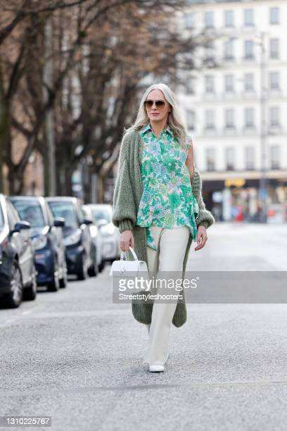 Best Ager Model and Influencer Petra van Bremen wearing a sage green long knitted coat by Maiami, a white and green floral print blouse without...