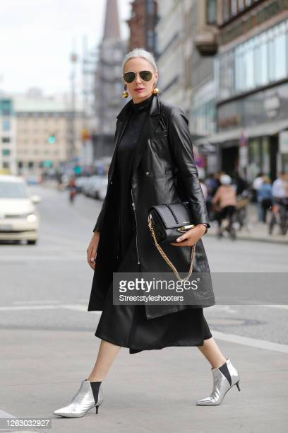 Best Ager Model and Influencer Petra van Bremen wearing silver ankle booties by Essential a long black dress by Maison Rabih Kayrouz a black leather...