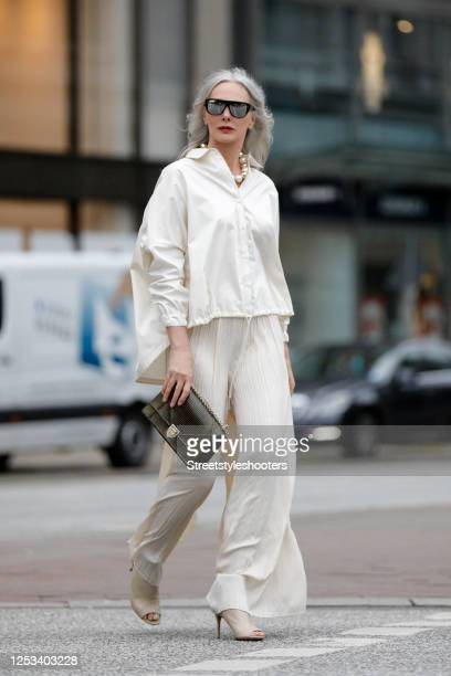 Best Ager Model and Influencer Petra van Bremen wearing sunglasses by Dior, a cream colored blouse by Zara, cream colored wide leg pleated pants by...