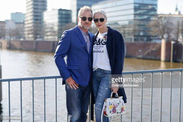 Best Ager Model and Influencer Petra van Bremen wearing sunglasses by Dior, a dark blue coat by Juvia, a white t-shirt with black logo print by Dolce...