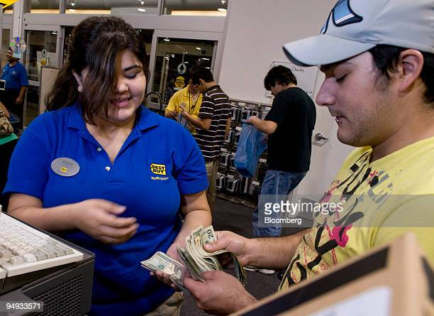 Best Buy cashier Amanda Rodriguez accepts cash from Daniel Garcia for his purchases at a store in Corpus Christi Texas US on Friday Nov 28 2008 US...