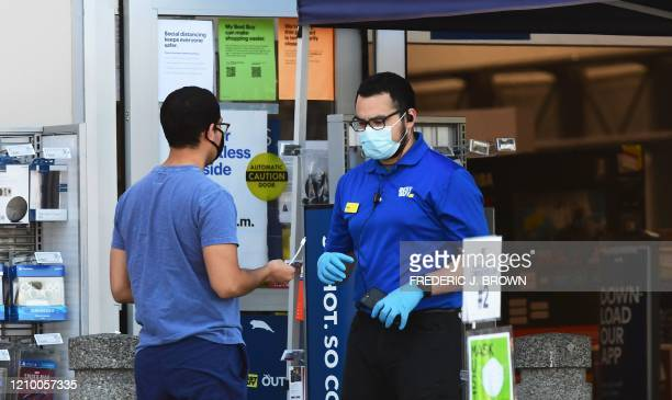 A Best Buy employee tends to a customer outside a store in Montebello California on April 15 2020 as the electronics nationwide chain store remains...