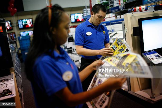 Best Buy employees study the sale ad before the store store opens on November 27 2009 in Fort Worth Texas According to the National Retail Federation...