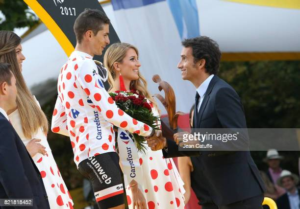 Best climber Warren Barguil of France and Team Sunweb receives the trophy from CEO of Carrefour Alexandre Bompard during the trophy ceremony...