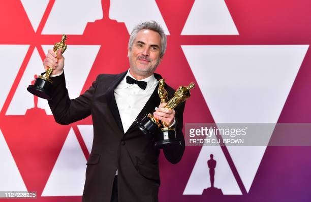 Best Director Best Foreign Language Film and Best Cinematography winner for Roma Alfonso Cuaron poses in the press room with his Oscars during the...