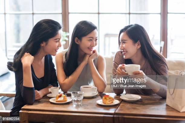 best female friends drinking coffee in caf¨¦ - donna cinese foto e immagini stock