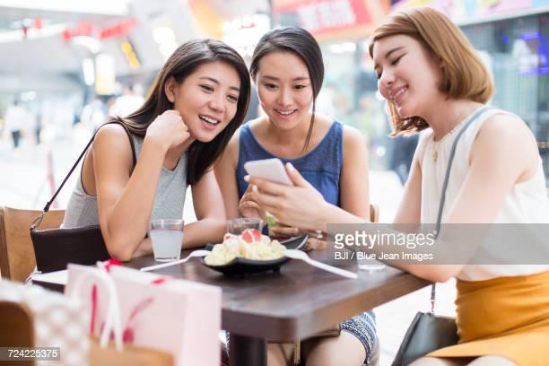 Best female friends sitting at sidewalk caf_