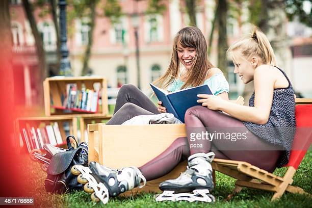 best friends bonding  and reading books at the city park