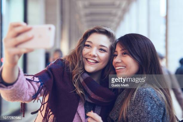 Best friends doing selfie in the city.